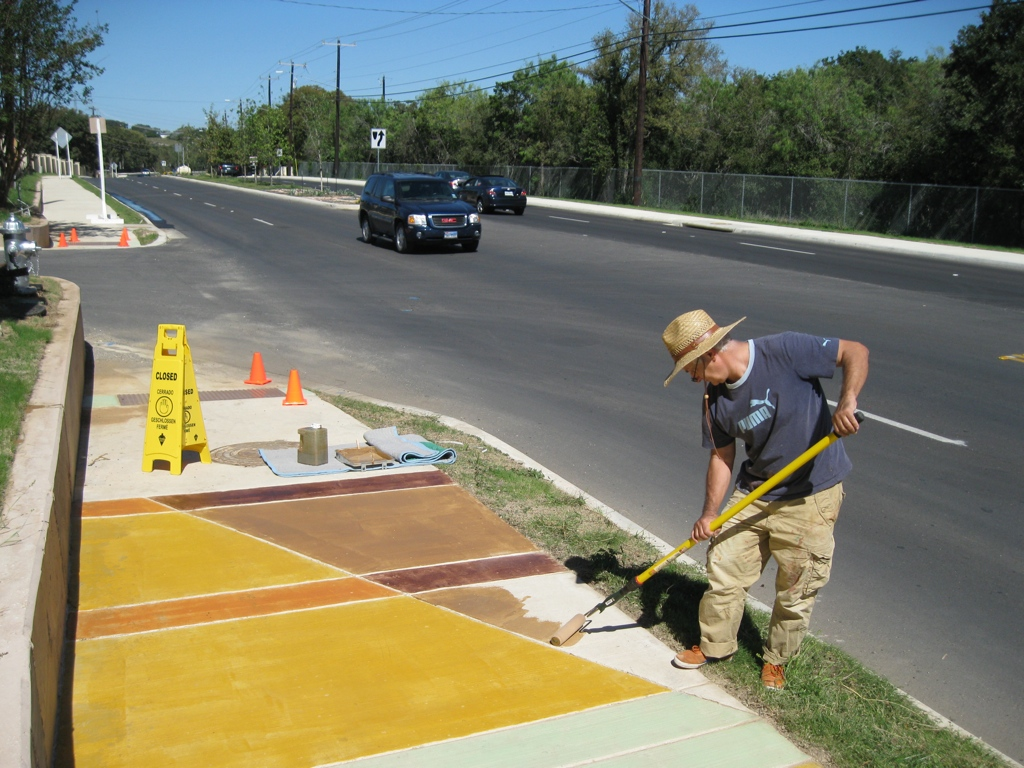 """Mark Schlesinger working on his 1.2 mile installation, """"Along Here & There,"""" on Jones-Maltsberger Road between Redland Road and Thousand Oaks Drive in San Antonio. Completed this year, the streetscape design includes hand-painted sidewalks, integral color concrete retaining walls, concrete guard and metal rails along a 200-foot mixed-use bridge. It also has colored utility covers. ADA ramps, and painted metal handrails. Photo by Elise Urrutia."""