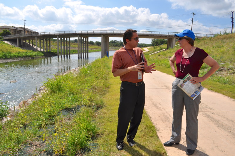 Steven Shauer of SARA talks with Nancy Stoner of the EPA about the work that's being done on the Mission Reach Ecosystem Restoration and Recreation Project at Roosevelt Park. Photo by Iris Dimmick.