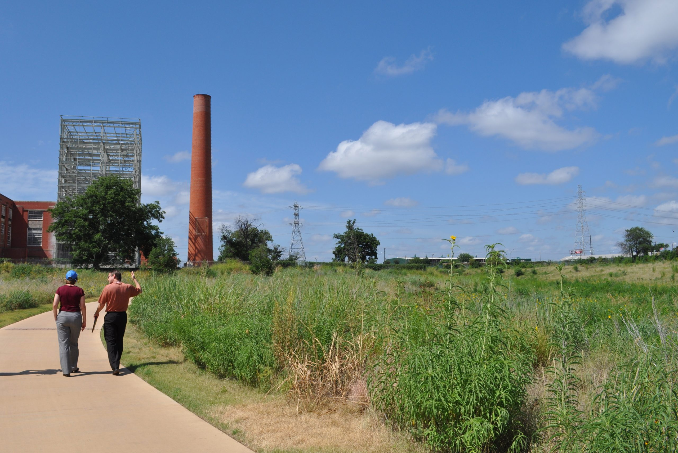 Steven Schauer, SARA spokesperson, knows the ins and outs of the Mission Reach and regularly gives casual, informative tours. Most recently, he showed off a stretch of the bike/walk trail near Roosevelt Park to an EPA official (pictured). Photo by Iris Dimmick.