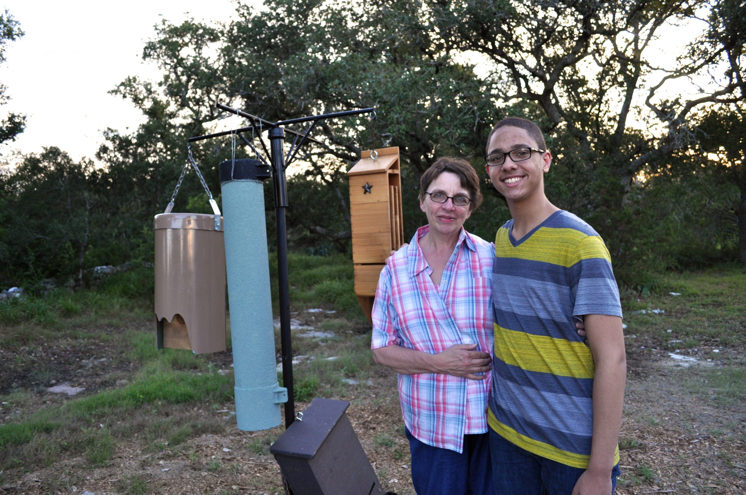 Roxanna and Chris Dean pose for a photo next to three examples of makeshift bat houses at Bracken Cave. Photo by Iris Dimmick.