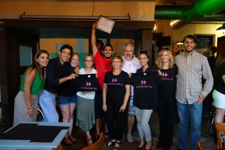 Edward Garcia holds up his $1,000 Awesome SA grant certificate for a photo with Awesome SA board and trustees. Courtesy photo.