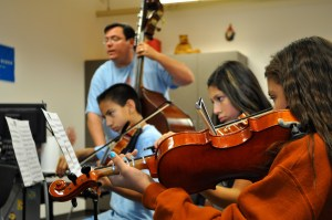 Young YOSA violinists play with Zeserman on bass while he monitors their progress. Photo by Iris Dimmick.