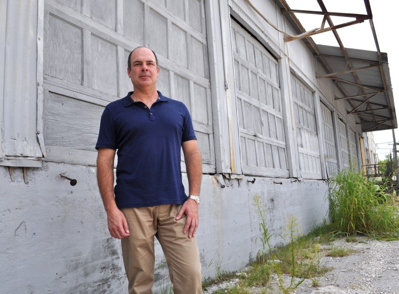 Developer Steve Yndo stands at his project site of East Quincy townhomes. The abandoned warehouse will soon be demolished to make way for 25 townhomes. Photo by Iris Dimmick.