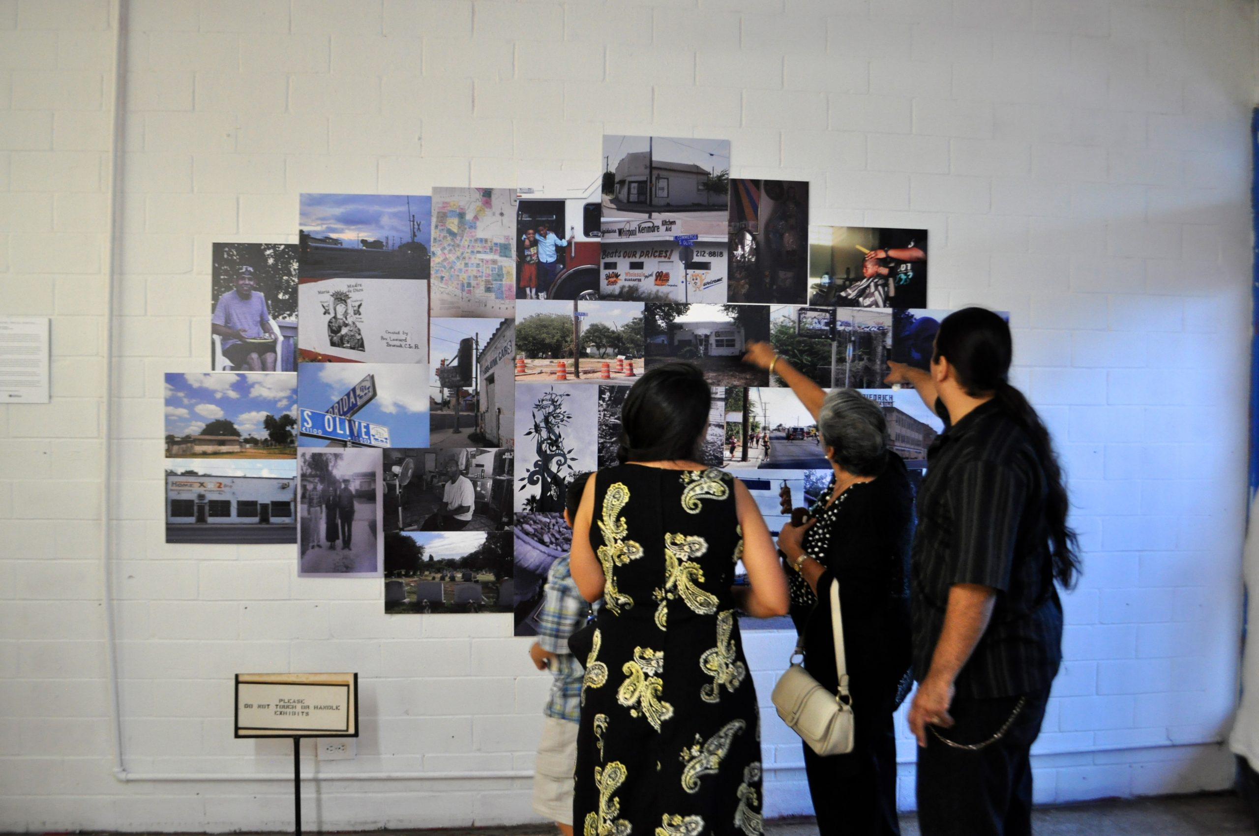 """Visitors examine photography documenting """"Eastside S.A."""" at The Movement Gallery and Underground Library. Photo by Iris Dimmick."""