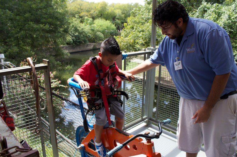 An attendant at the Witte Museum assists a youngster on the popular SkyCycle.