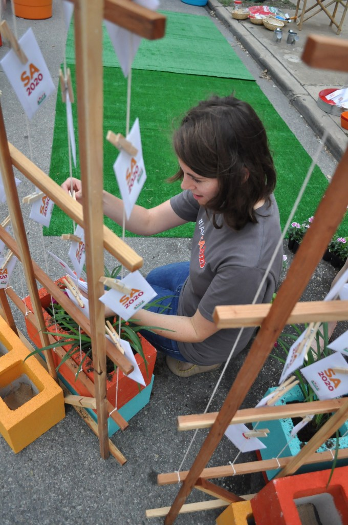 A member of the SA2020 team hangs packets of wildflower seeds at the group's spot on PARK(ing) Day in downtown San Antonio. Photo by Annette Crawford.