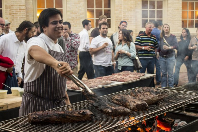 Chef Michael Toscano of Perla restaurant in New York City, tends meat on the grill. Photo by Jesse Torres.