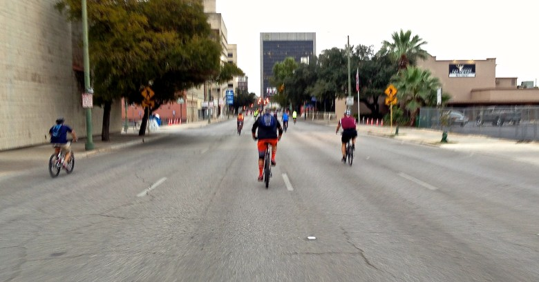 Cyclists pedal empty downtown streets.