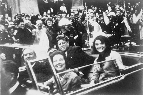 John and Jackie Kennedy in the presidential limousine before the assassination. Public domain image.