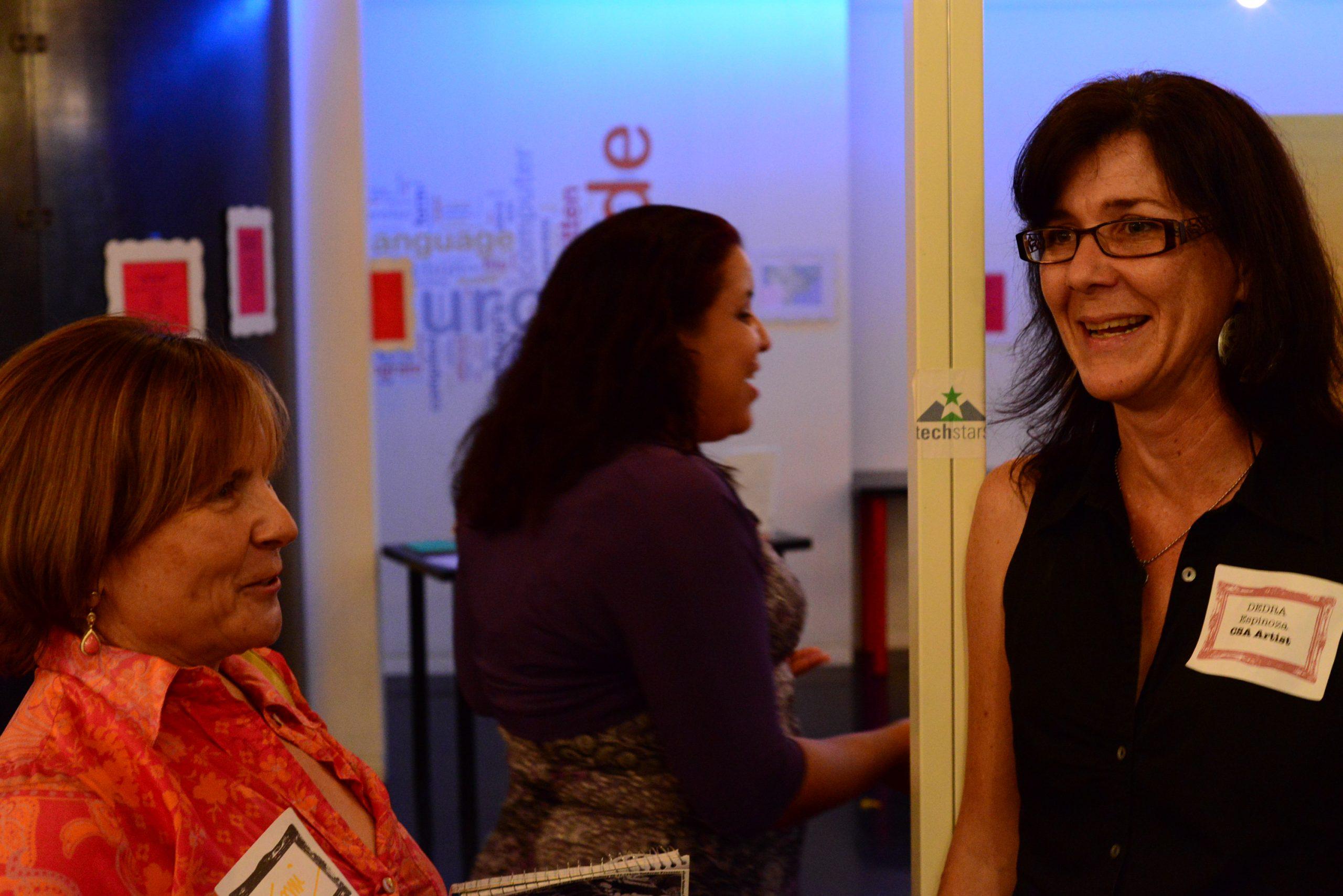 Tami Kegley talking with Dedra Espinoza at the CSA Kickoff Party, August 2013. Photo by Page Graham.