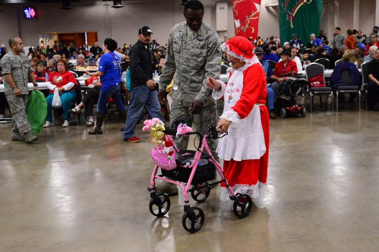 """""""Mrs. Claus"""" joins an Air Force Airman in a cumbia dance. Photo by Page Graham."""