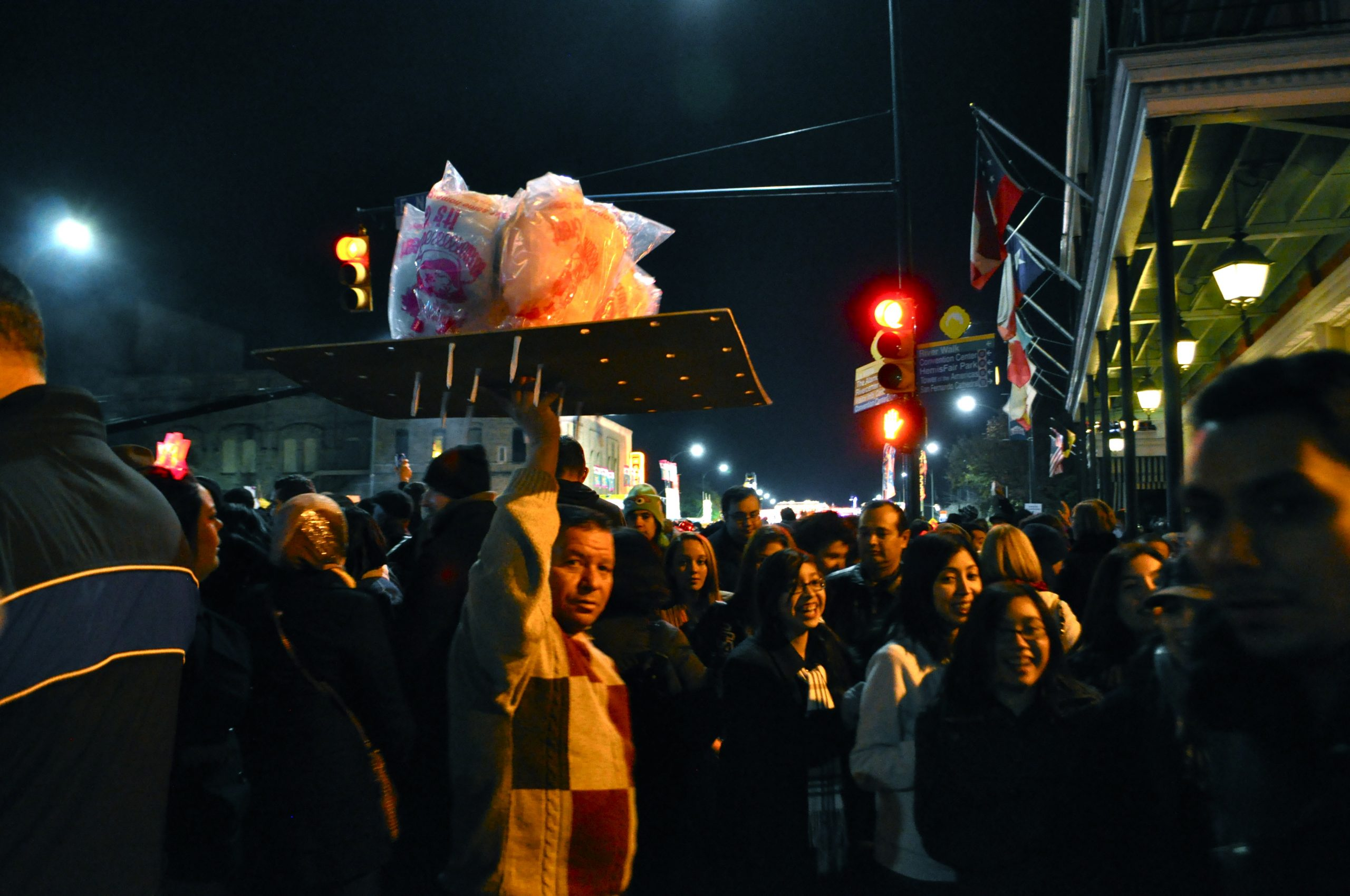 A cotton candy vendor makes his way through thousands of New Year's Eve revelers gathered on South Alamo Street in downtown San Antonio on Dec. 31, 2013.