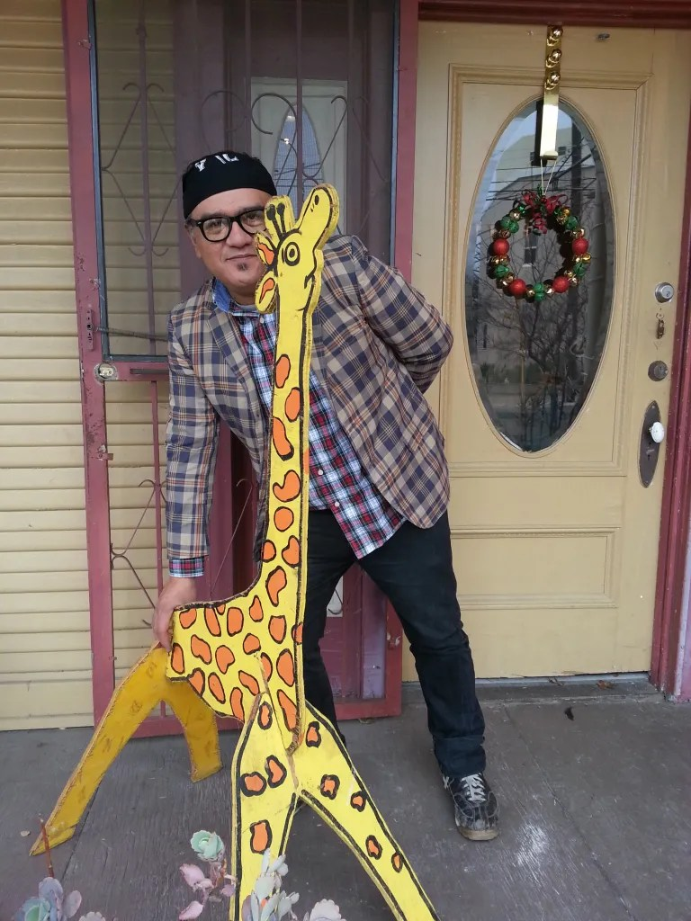 Agosto Cuellar poses with his vividly colored giraffes. Photo by Kevin Tobar Pesantez.