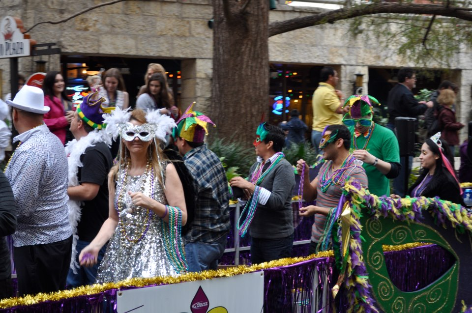 Dozens of river barges filled with costumed bead-tossers pass by crowds of revelers for the 2013 Mardi Gras River Parade. Photo by Iris Dimmick