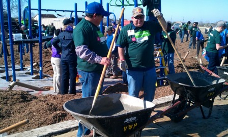 Volunteers mix concrete for the new playground at Brooks Park. Photo by Andrew Moore.