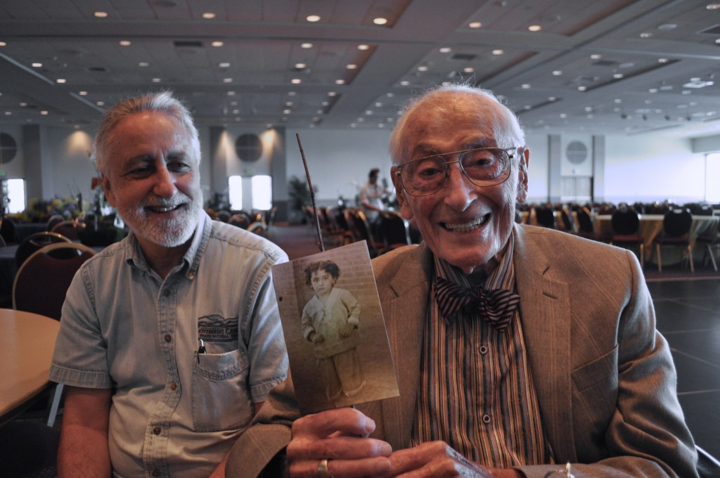 Lanny Sinkin (left) sits with his father, Bill Sinkin, who turned 100 on May 19, 2013 and passed away Feb. 3, 2014. Bill holds a photo of himself wearing the velvet suit he wore to school at age six. Photo by Iris Dimmick.