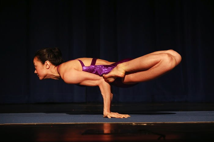 """Adult Female First Place recipient Gloria Suen executes a modified """"Peacock"""" pose during the 2014 National USA Yoga Asana Championship at the Aztec Theatre March 14-16. Photos by Stacy Pape/USA Yoga Federation."""