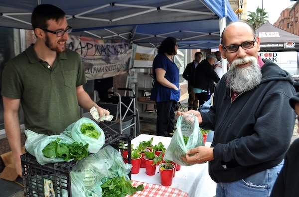 Rudy Benitez purchases a bag of hydroponically-grown spring mix from LocalSprout founder Mitch Hagney. Photo by Iris Dimmick.
