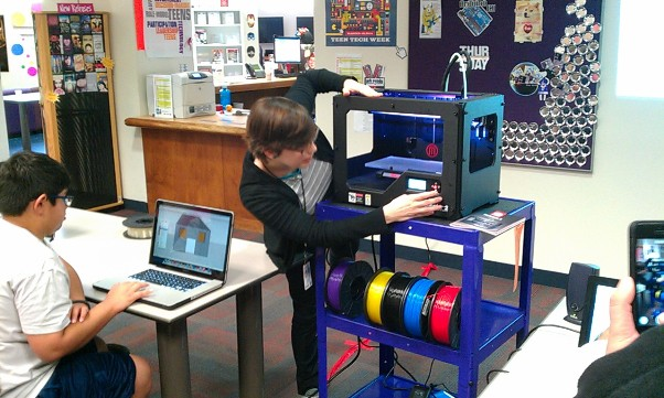 Teen Services coordinator Caroline Mossing sets up the brand new 3D printer at the Central Library. Photo by Andrew Moore.