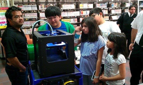 Teens watch the 3D printer in action at the Central Library. Photo by Andrew Moore.