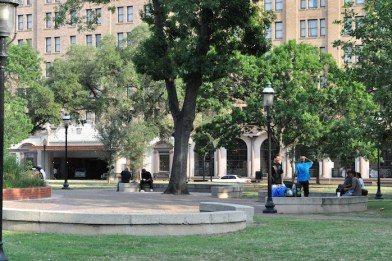 A few groups of people loudly congregate on the benches of Travis Park in May 2013. Photo by Iris Dimmick.