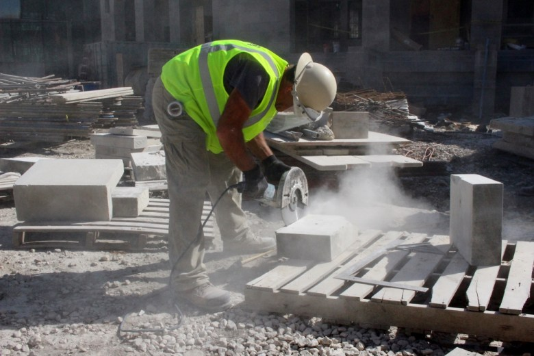A construction worker cuts limestone blocks that match the facade of the original Municipal Auditorium. Photo by Page Graham.