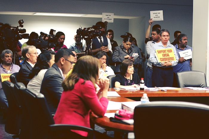 """Taxi drivers and media crowd the Public Safety Committee meeting room to hear talks about how authorities will deal with """"rideshare""""/transportation network companies. Photo by Iris Brandy Rae Perez."""