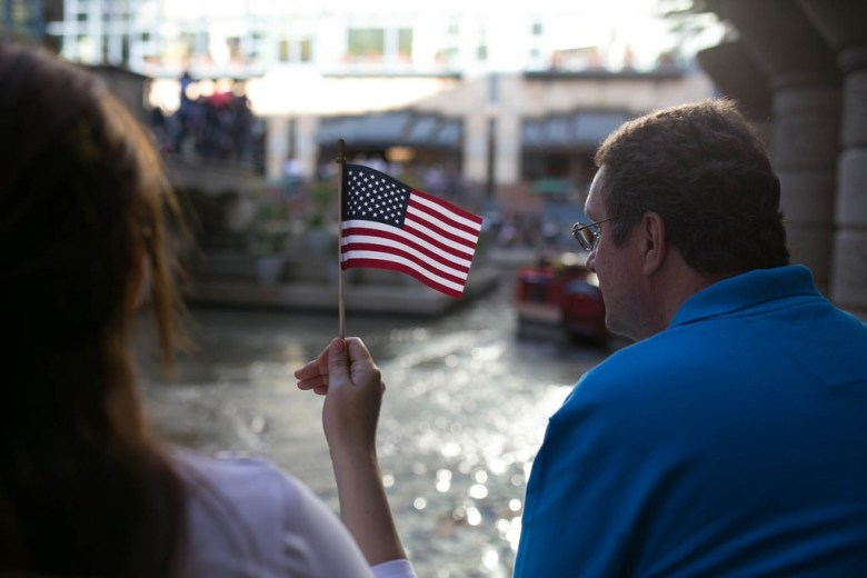 A parade attendee waves an American flag during the Armed Forces parade in 2014.