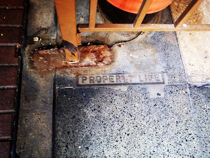 The original property line of the Empire Theatre, now on the sidewalk near Starbucks. Photo by Miles Terracina.