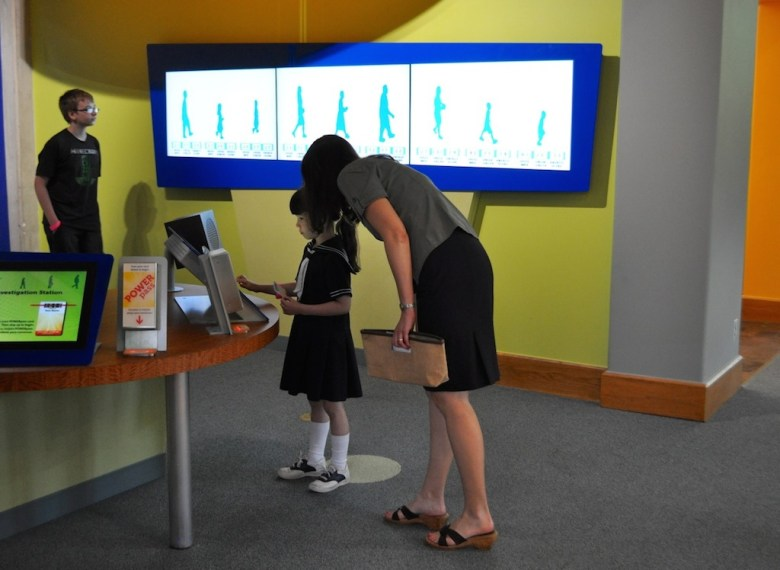 """A family tries out the """"Pick Up Your Pace"""" investigation station during the Witte Museum H-E-B Body Adventure media preview event May 23, 2014. Photo by Iris Dimmick."""