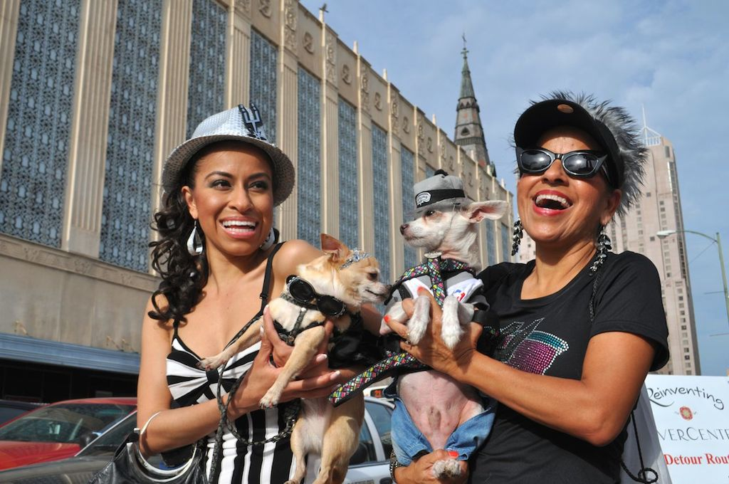 """Kristen Rodriguez holds """"Coco"""" (left) and poses for a photo with Thelma Rodriguez and """"Calvin"""" on their way to the 2014 Spurs Championship River Parade on June 30, 2014. Photo by Iris Dimmick."""