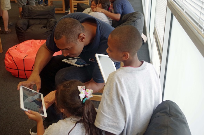 Boris Diaw helps students explore brand new tablets during a press conference announcing a new Spur-sponsored Learn and Play Center at Bowden Elementary School on June 6, 2014. Photo by Juan Garcia.