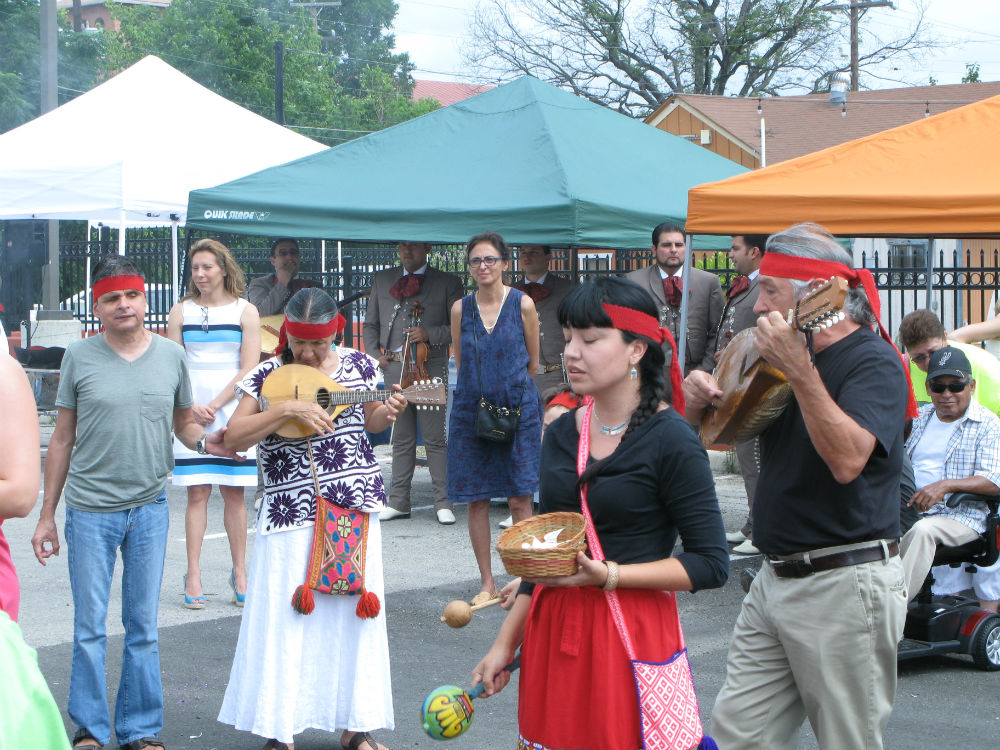 Patty Ortiz (center) observes the Grupo de Danza Azteca Xinachtli performing a blessing over WestFest on June 21, 2014. Photo by Katie Nickas.