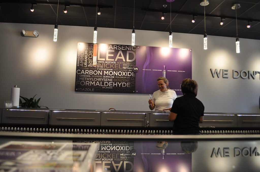 """Belinda Kennedy talks with a Monster Vape employee about different nicotine milliliter options for her new vaporizer. She walked out of the store paying about $70 for a complete set including a battery, an e-juice, and the vaporizer itself. ____ is only a social smoker, """"but it's enough to make me feel it the next day."""" She said she thinks vaporizing rules are left up to business owners to decide, not the government. Photo by Iris Dimmick."""
