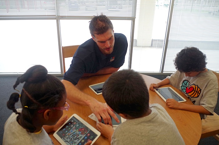 Tiago Splitter helps students explore brand new tablets after a press conference announcing a new NBA-sponsored Learn and Play Center at the Bowden Elementary School on June 6, 2014. Photo by Juan Garcia.
