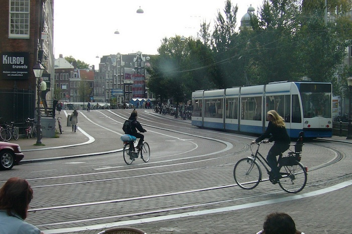 Looking out a streetcar window at cyclists in Amsterdam. Photo used with permission from Flickr user deltrems.