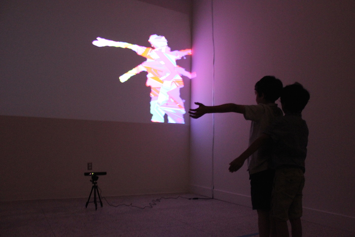 """Brothers manipulate their virtual portraits in Cisco Merel's interactive piece titled """"Self-Portrait"""" at the Guadalupe Cultural Arts Center's exhibit, """"Flatland."""" July 11, 2014. Photo by Melanie Robinson."""