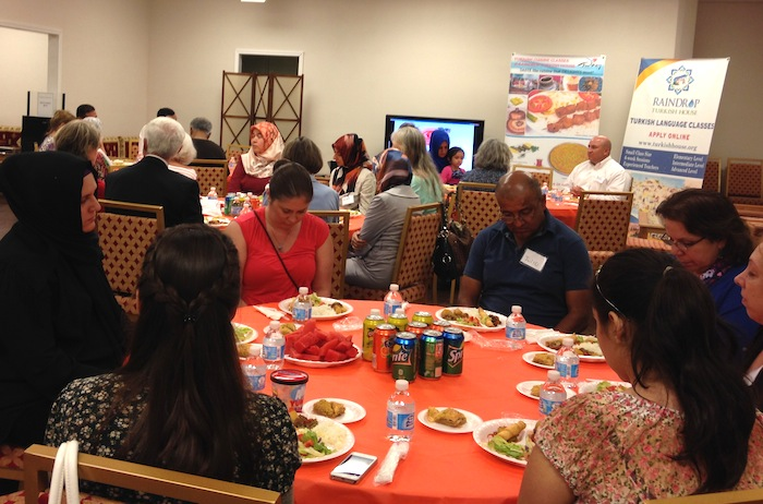 Guests bow their heads before sharing a Ramadan dinner at Raindrop Turkish House. Photo by Martha Ann Kirk.
