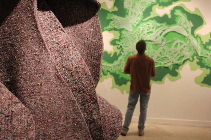 "A visitor observes local and international art at the Guadalupe Cultural Arts Center's exhibit, ""Flatland"" exhibit. July 11, 2014. Photo by Melanie Robinson."