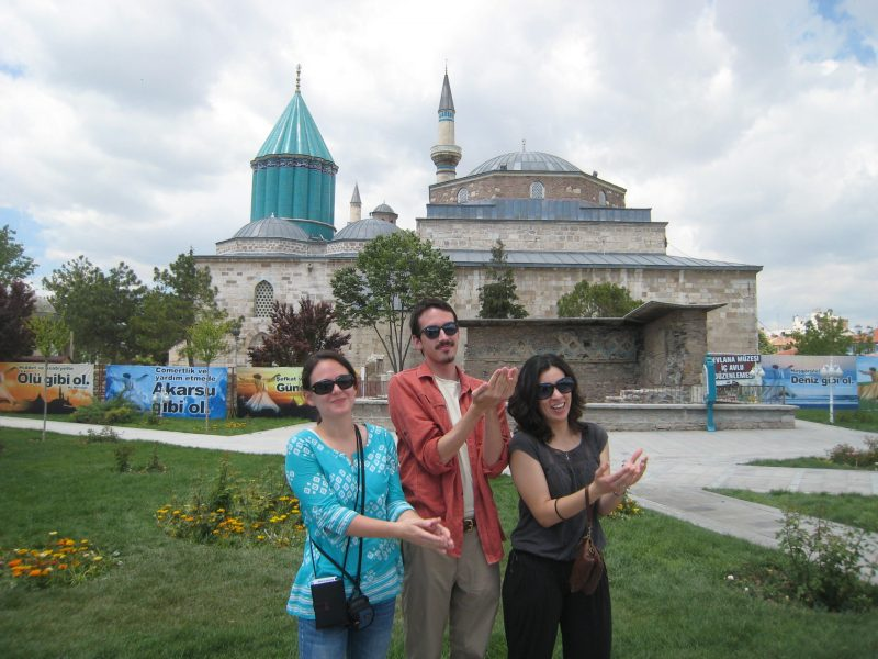Jessica Glover, Troy Steen, and Denisse Ibarra pose for a photo beside the mosque over Rumi's tomb.