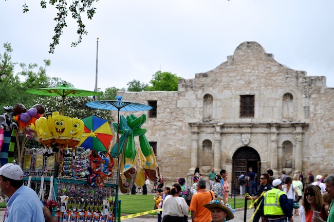A street vendor pulls his cart of merchandise amid tourists and locals in front of the Alamo before the 2013 Battle of the Flowers Parade. Photo by Iris Dimmick.
