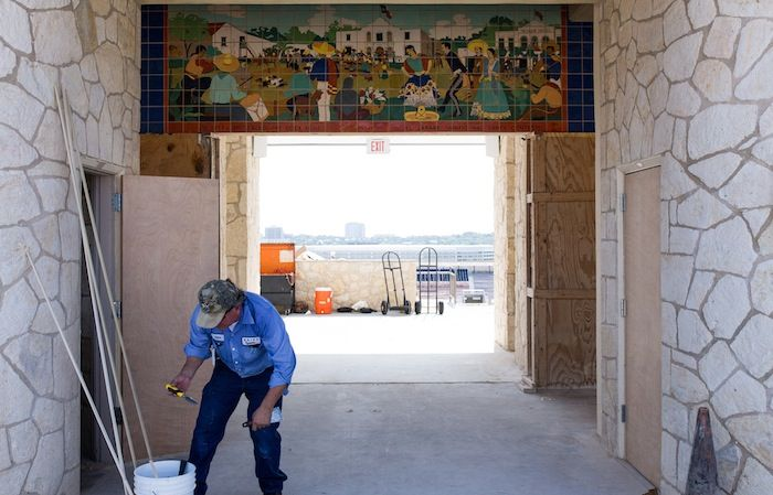 A worker cleans up his job site underneath the preserved Murals at the entrance to Alamo Stadium. Photo by Scott Ball.