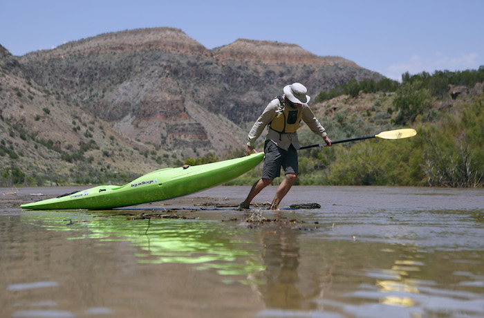 WHITE ROCK CANYON, NM - Colin McDonald hauls his kayak over the growing delta that is building at the head of Cochiti Reservoir in White Rock Canyon in New Mexico. JULY 24, 2014: CREDIT: Erich Schlegel/Disappearing Rio Grande Expedition