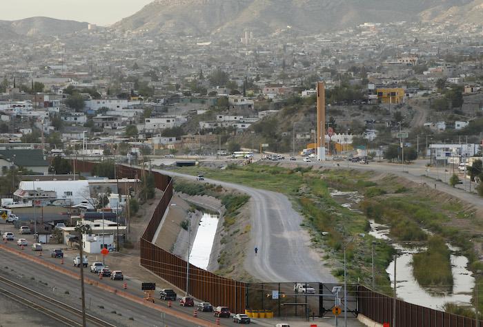 EL PASO, TX - Colin McDonald walks inside the border fence in El Paso, Texas. Ciudad Juarez, Mexico is in the background. SEPTEMBER 15, 2014 CREDIT: Erich Schlegel/Disappearing Rio Grande Expedition