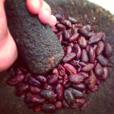 The chefs make chocolate from cocoa beans. After toasting the beans, they make a paste using a metate or a molcajete.