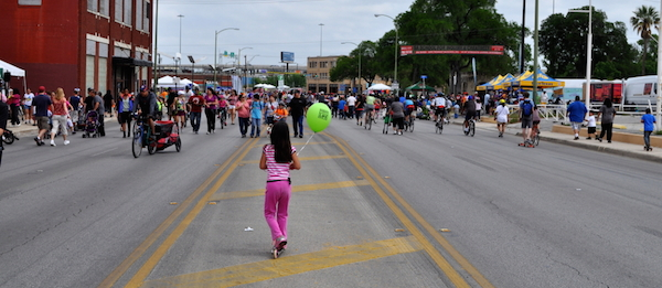 A girl rides a Razor scooter down the center of Broadway Street during Síclovía 2013. Photo by Iris Dimmick.