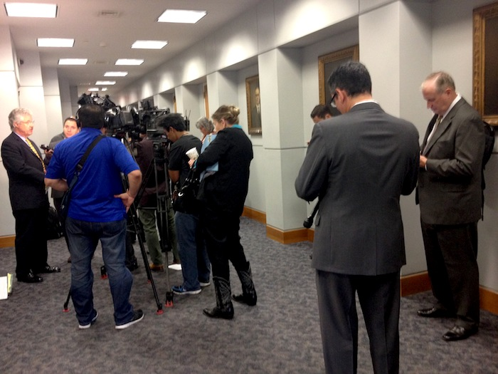 Ron DeLord, the lead negotiator for the police union (right), looks on as Jeff Londa, Houston lawyer representing the City of San Antonio, stands amid a huddle of television cameras and describes the union proposal as untenable. Photo by Robert Rivard.