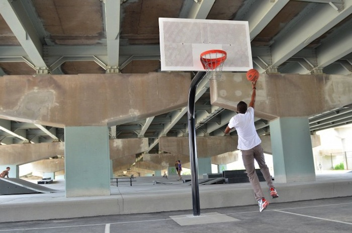 Part of Toronto's Underpass Park includes basketball courts and a skate park next to the concrete support columns. Photo Courtesy of Waterfront Toronto.
