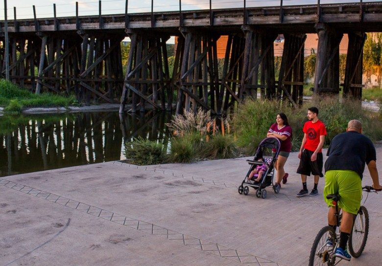 A cyclist passes a family while taking a stroll on the Mission Reach at sunset. Photo by Scott Ball.
