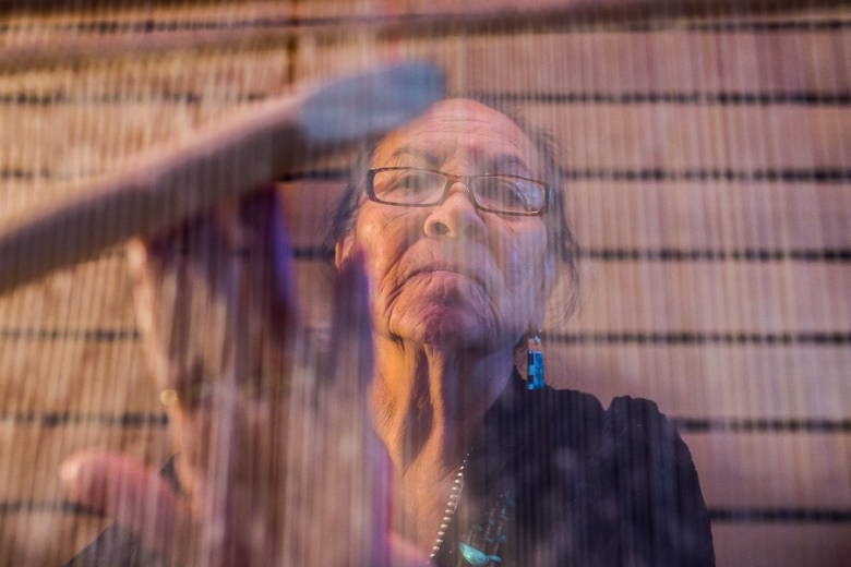 Strings cascade in front of Navajo weaver Nanabah Aragon at the inaugural Yanaguana Indian Arts Market. Photo by Scott Ball.